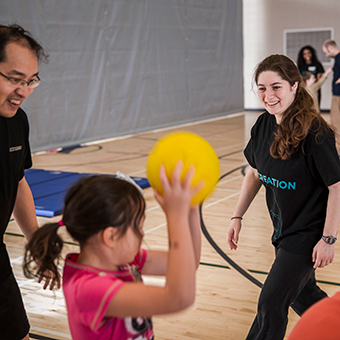 Recreation student leads activity in gym with children.