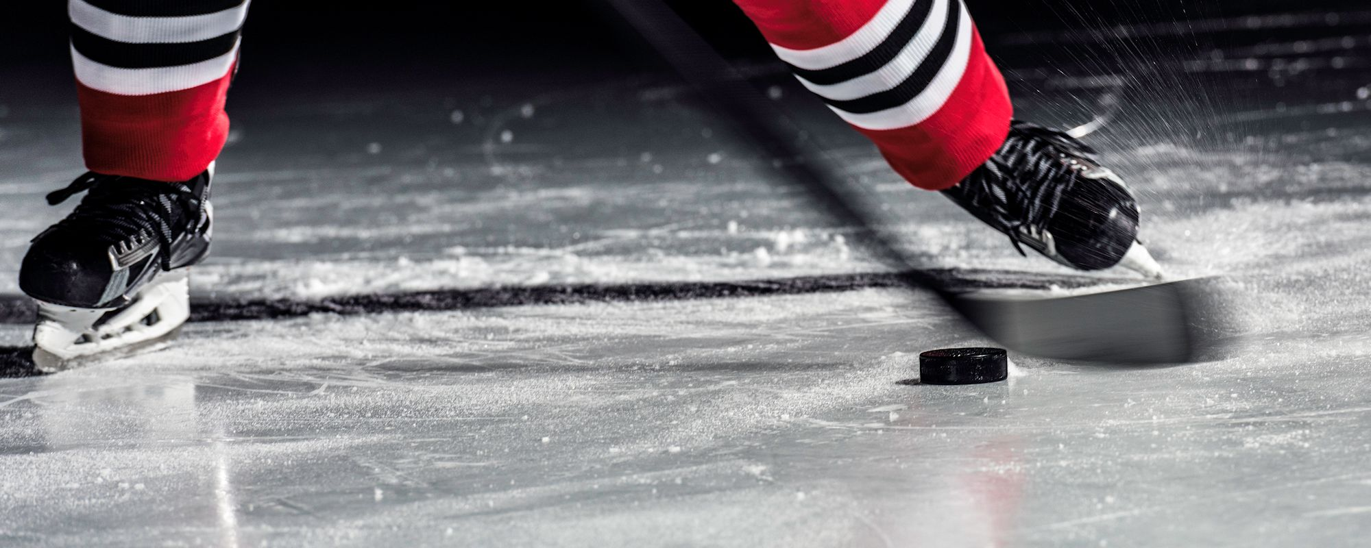 Hockey player skates with stick and puck on ice