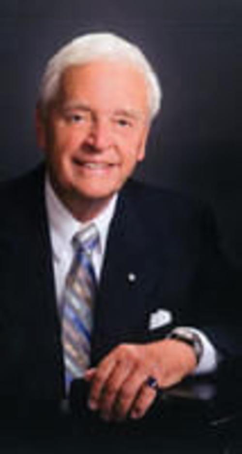 A man, Richard DUmbrille, posing for a portrait-style photo