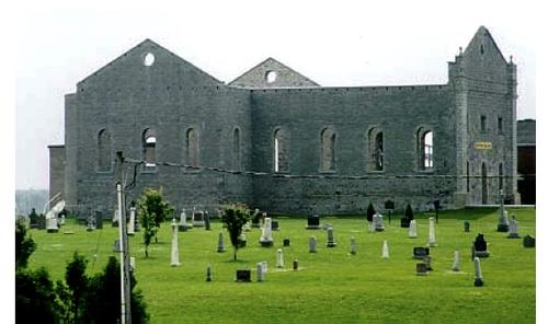 Neglected church ruins, walls intact, roofless, with graveyard in front