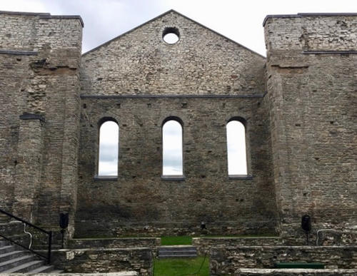 Church transept, stone wall with windows, no roof and stairs