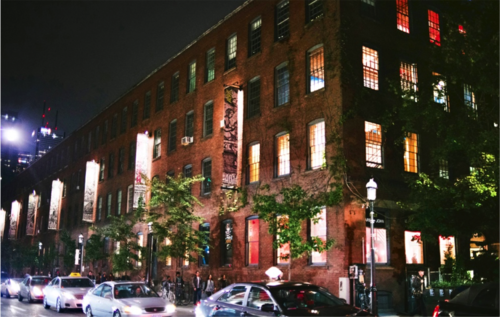 An image of a red brick building on a busy street at night, 401 Richmond
