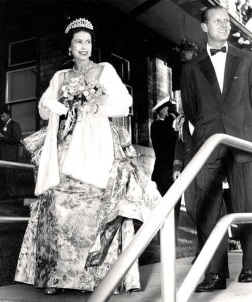 A black and white image from 1959 of the Queen and Prince Phillip visiting Stratford, walking down steps with the queen holding flowers and the prince in a tuxedo