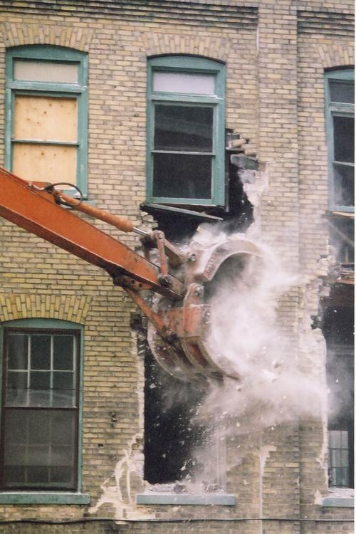 The arm of a bulldozer tearing down a stone building