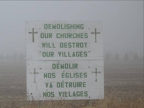 A sign stating - Demolishing our churches will destroy our villages - in English and French.
