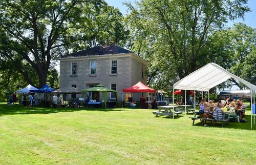 A stone farmhouse during the day with an event going on; people sitting under tents and eating