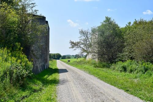 Bridge abutments with a gravel road between them.