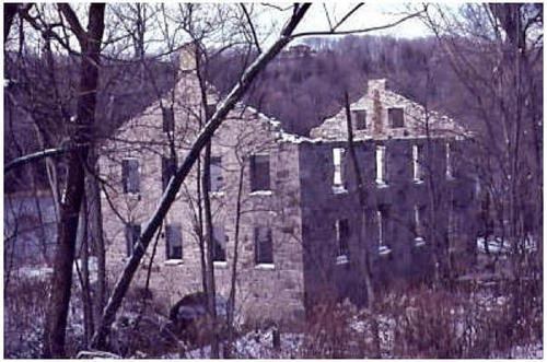 An abandoned mill without roof or glass windows.