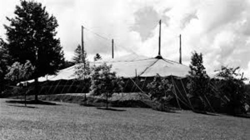 A black and white historic photo of a large tent raised in Queen's Park, Stratford