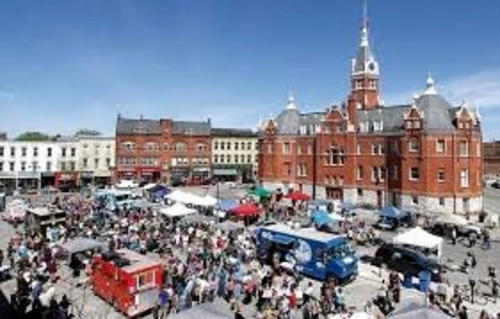 Stratforf City hall building and the market square busy with people and vendors