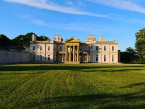 The front of a castle named Dundurn Castle from Hamilton with a large green lawn in front