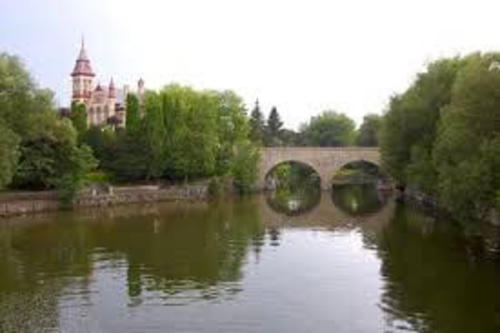 A landscape image showing stratford, a bridge over water and buildings in the background