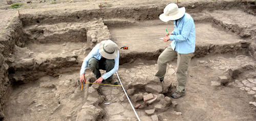 Two archaeologists working in an excavation dig site, measuring artifacts