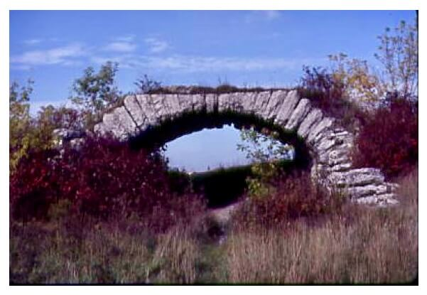 Ruined and neglected stone bridge covered in weed growth