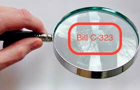 "A hand holding a magnifying glass with the words ""Bill C-323"" in red placed in the center"