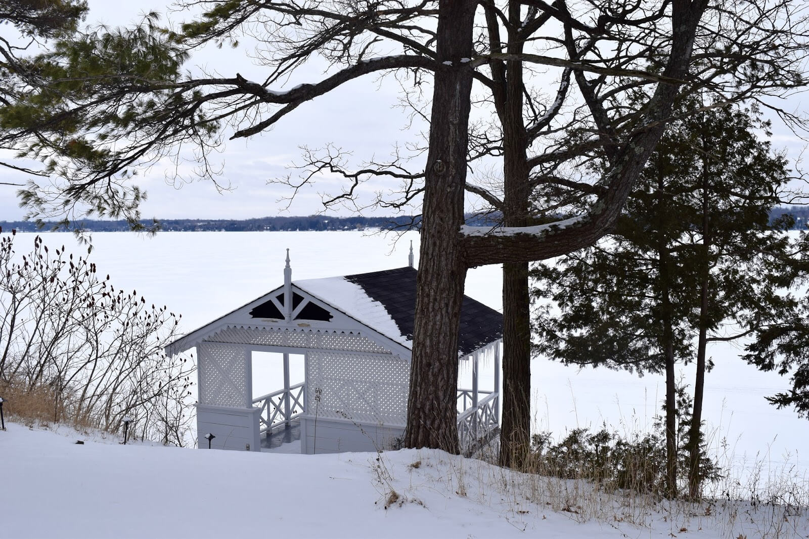 A boathouse on a frozen lake in the winter time