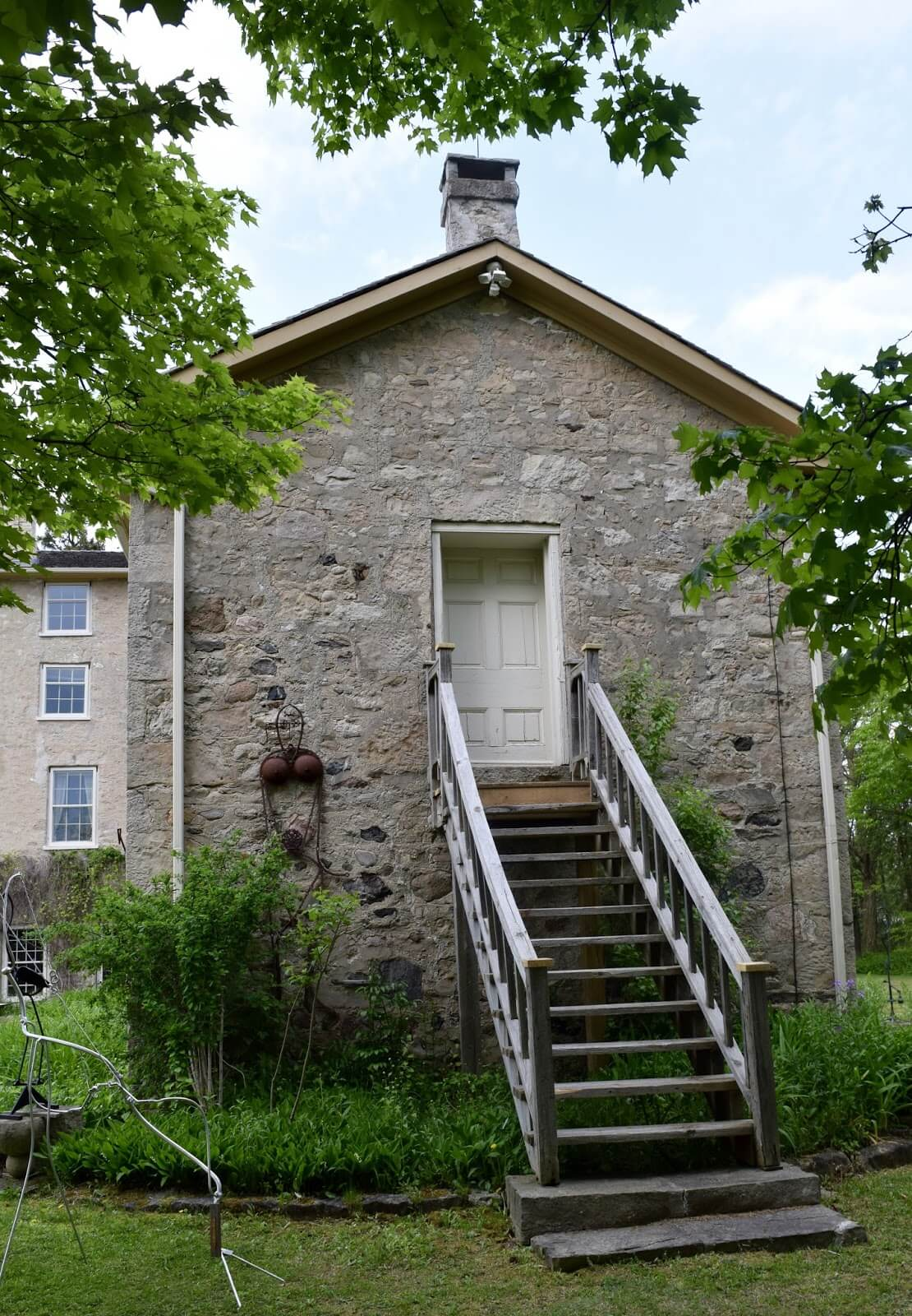 A rear perspective of the gynasium wing at Rockwod Academy, a historic stone building with staircase leading up to a door
