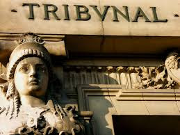 "A stone statue of a woman in front of a stone building with the word ""tribunal"" in-scripted on it"