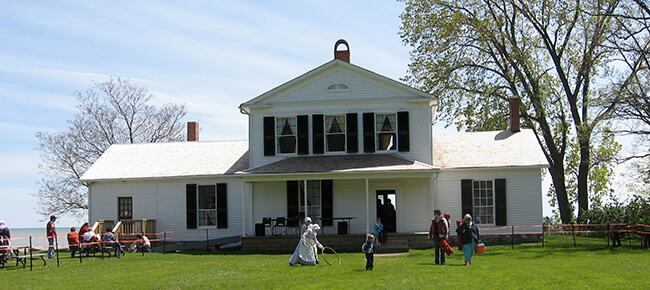 A white house dating back to 1842 with people playing in the front yard at John R. Park Homestead near Kingsville