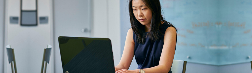 Female student in business casual wear working on a computer