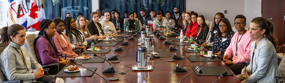 co-op students sitting around board room table with flags at ISED