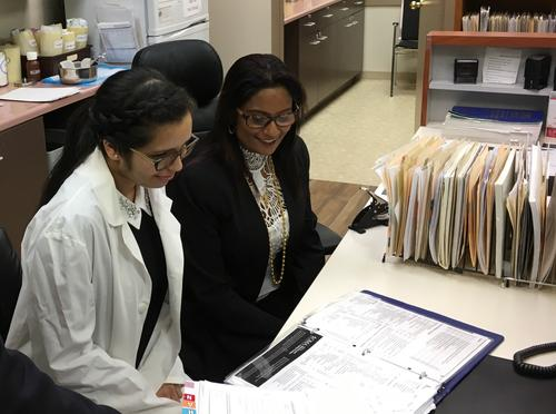 Co-op student Jashandeep Sohal reviews test results at the Waterloo Walk-in Clinic with owners Rex and Meera Mohamed.
