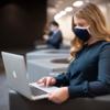 girl sitting at computer wearing mask