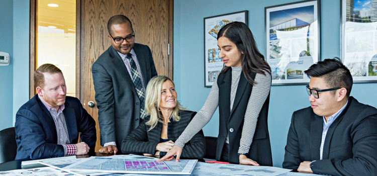 Debra Kakaria working with co-workers at MacNaughton Hermsen Britton Clarkson Planning Limited (MHBC)