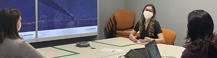 Co-op student, Vanessa Vanpopic sitting at table in meeting room with two of her colleagues.