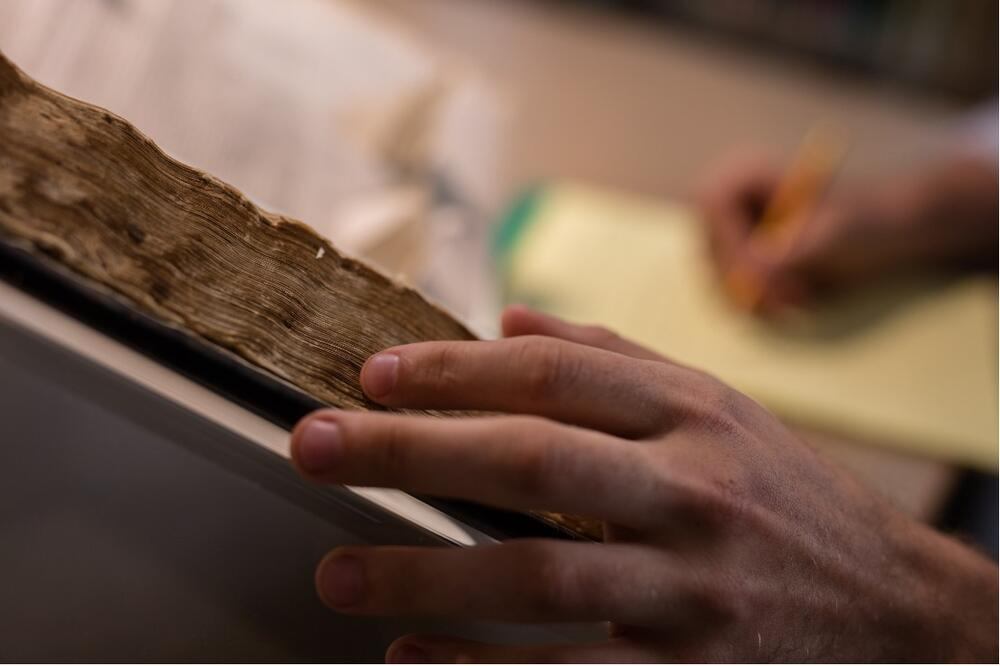 A close-up of an archived book, with the reader taking notes
