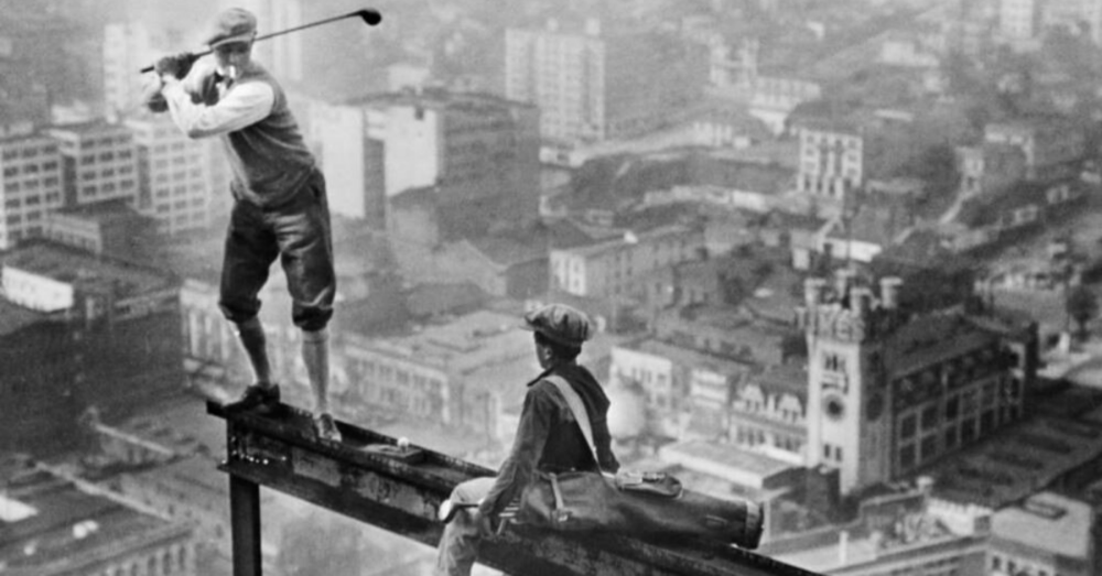 Two boys on beam driving a golf ball high above the city