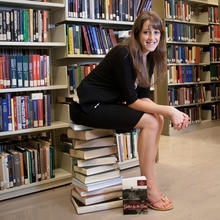 girl sitting on a stack of books in the library