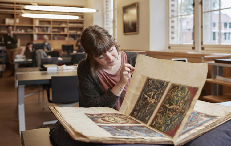 Historical researcher examining maps