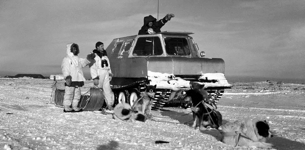 Photo of Arctic landscape with snow tank, people, sled and sled dogs