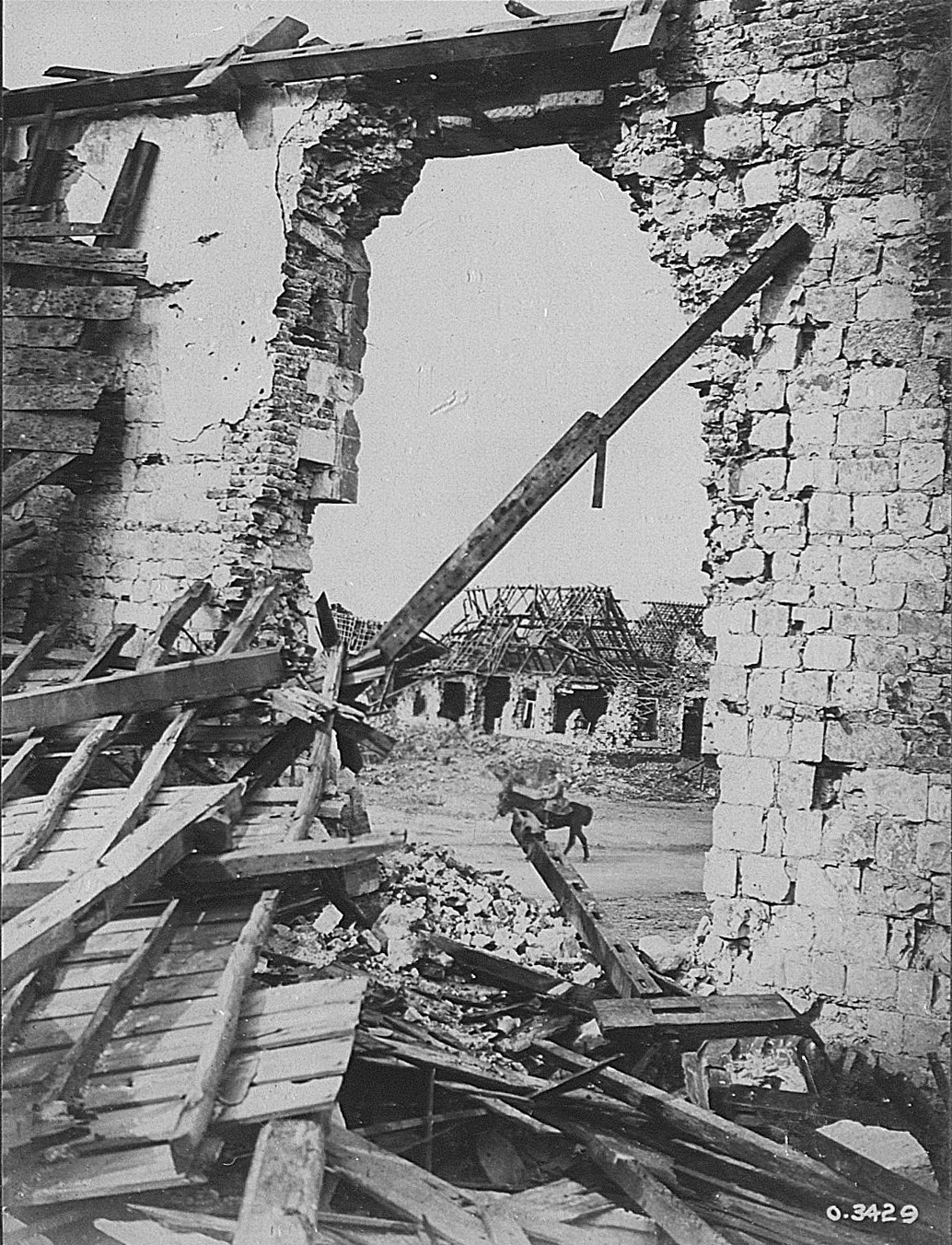 A lone cavalry officer rides through a ruined village