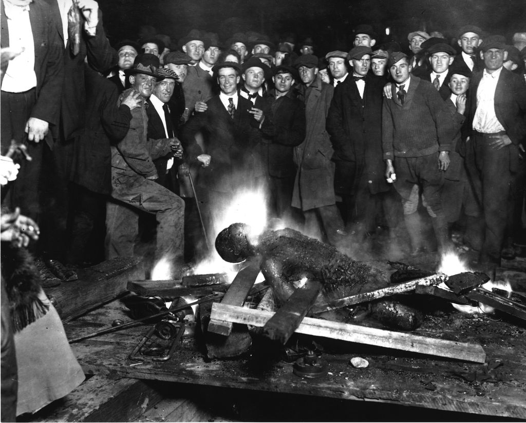 A group of white men gather around a burning African-American individual.