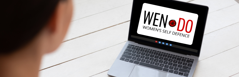 Woman looking at computer screen with the Wen-Do logo