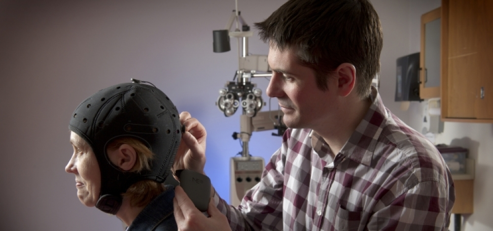Professor Ben Thompson applies transcranial direct current stimulation using a simple cap fitted on the patient's head.