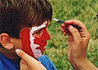 [Child getting Canadian flag painted on face]