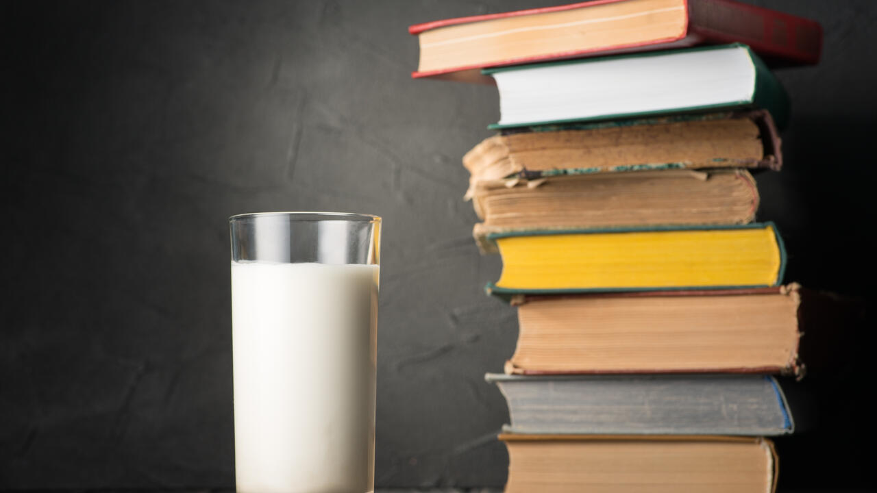 glass of milk stands next to pile of old books