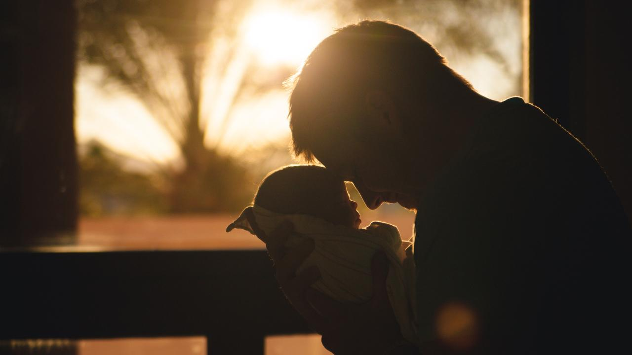 Man with baby at sunset