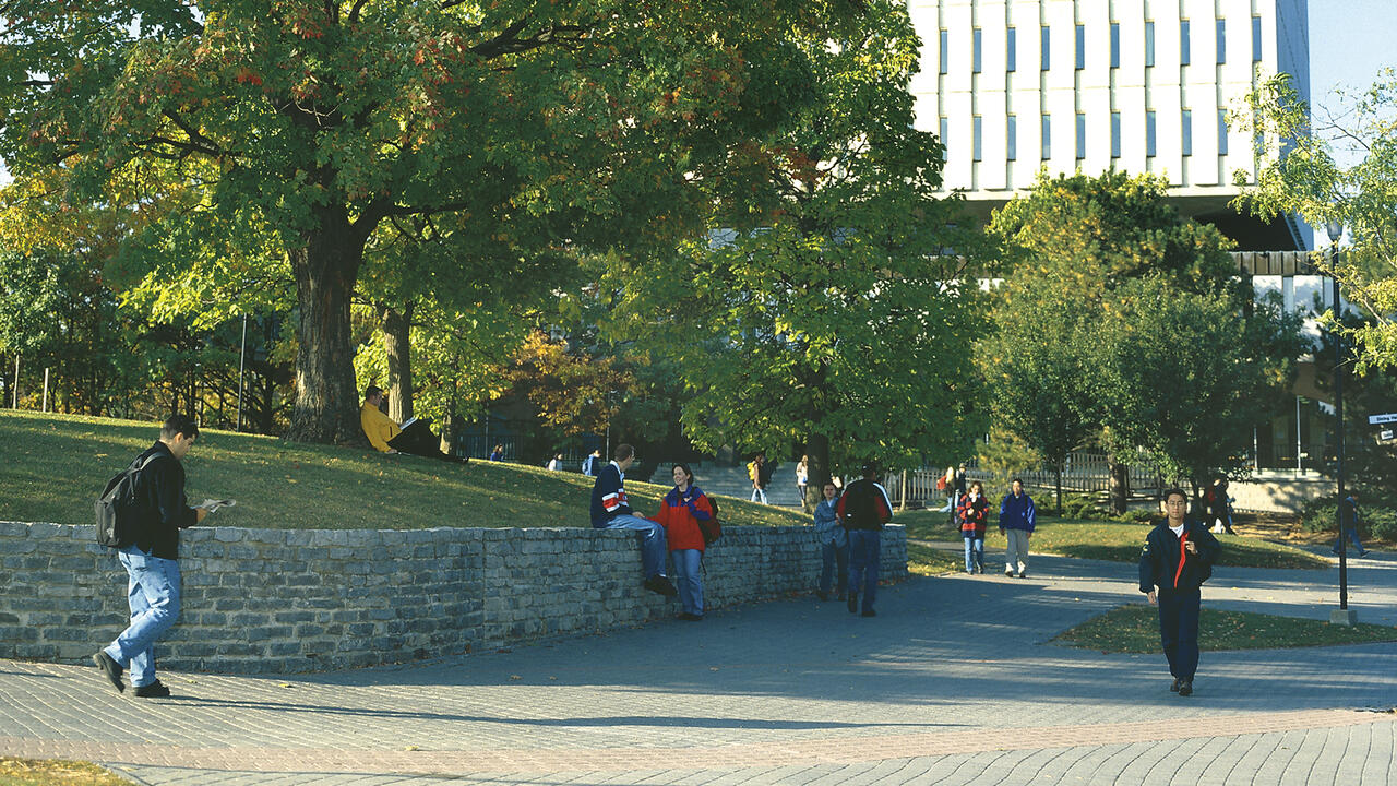 A photo of students walking by Dana Porter Library