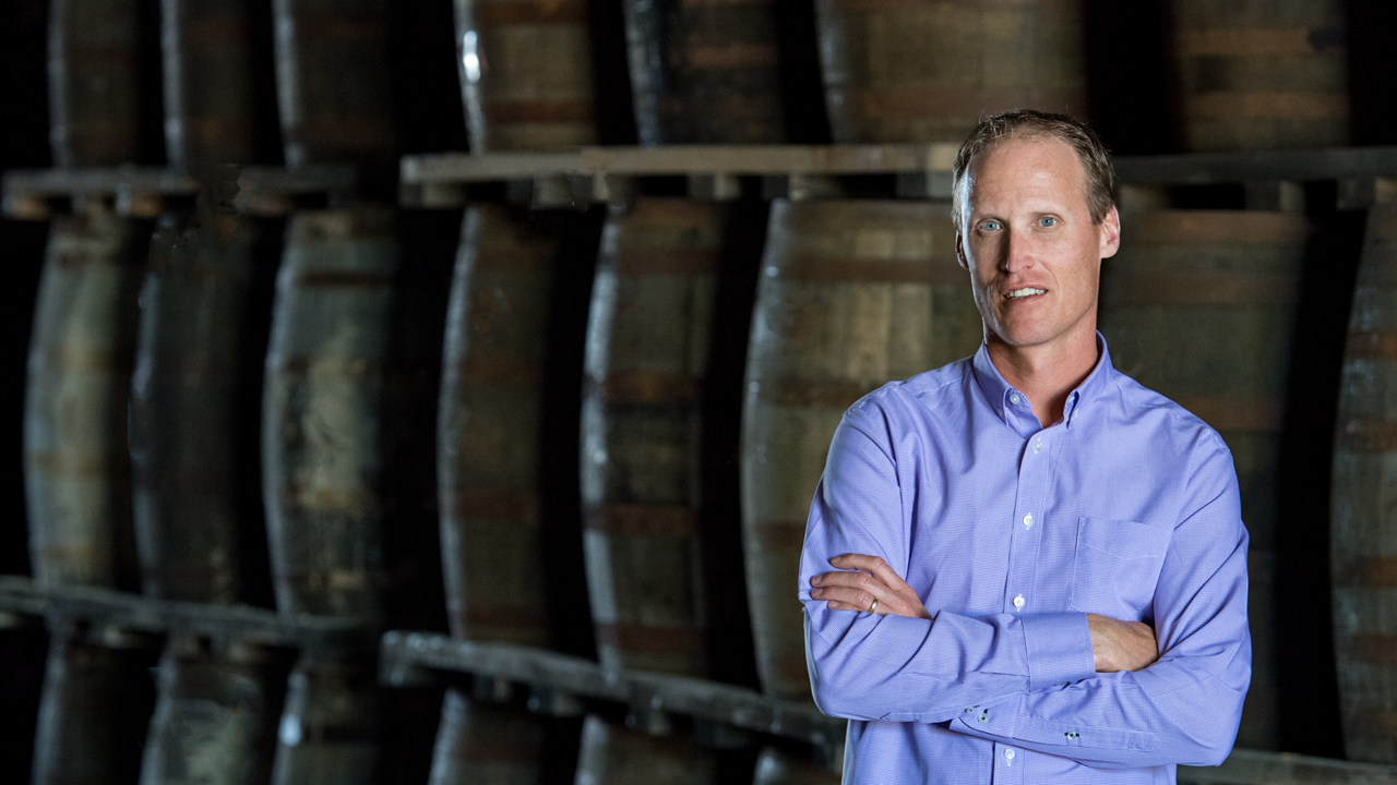 Don Livermore stands, arms crossed, in front of a row of whisky barrels