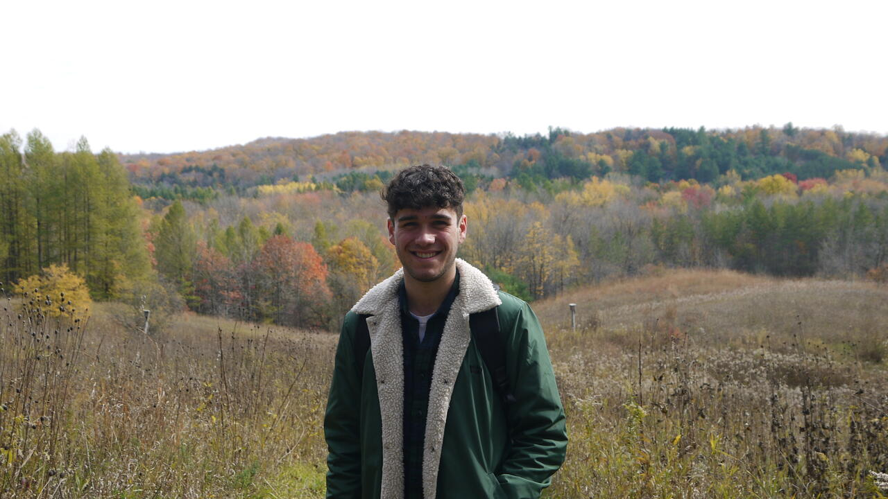 Ethan stands in a meadow in autumn