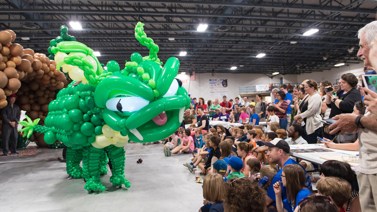 Audience marvels at a life-size balloon dragon