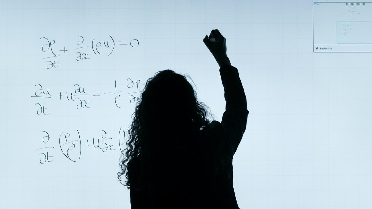 Silhouette of a woman, writing equations on a white background