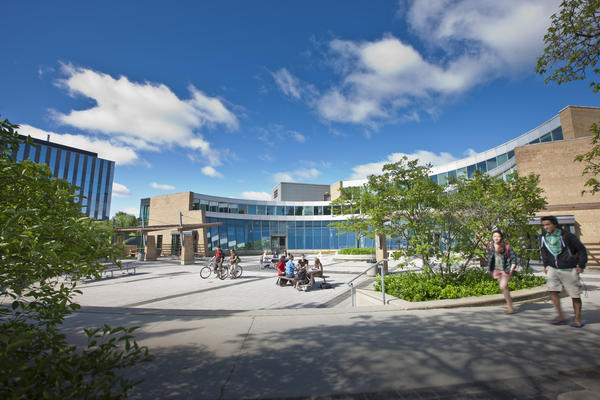 Students walk and sit outside the Student Life Centre