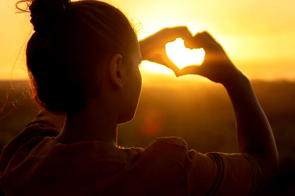 Young woman making a heart with her hands in front of the sun