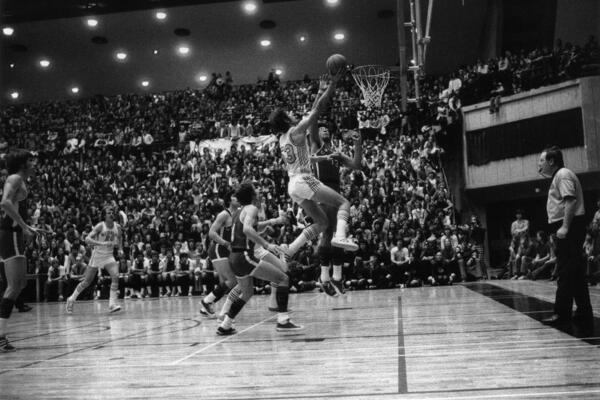 Mike Moser jumps in the air to shoot a layup with a large crowd in the stands