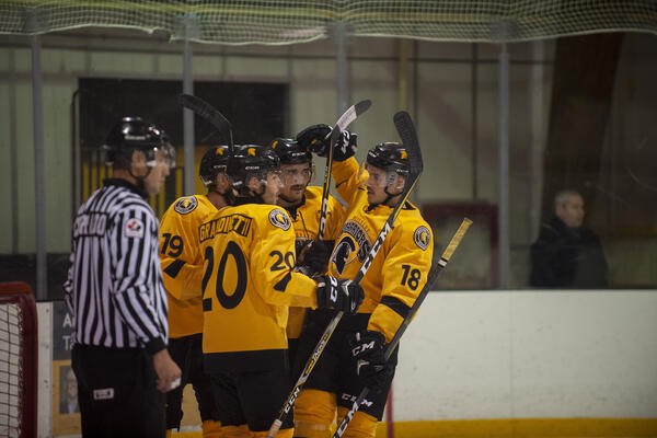 Men's hockey players gather on the ice